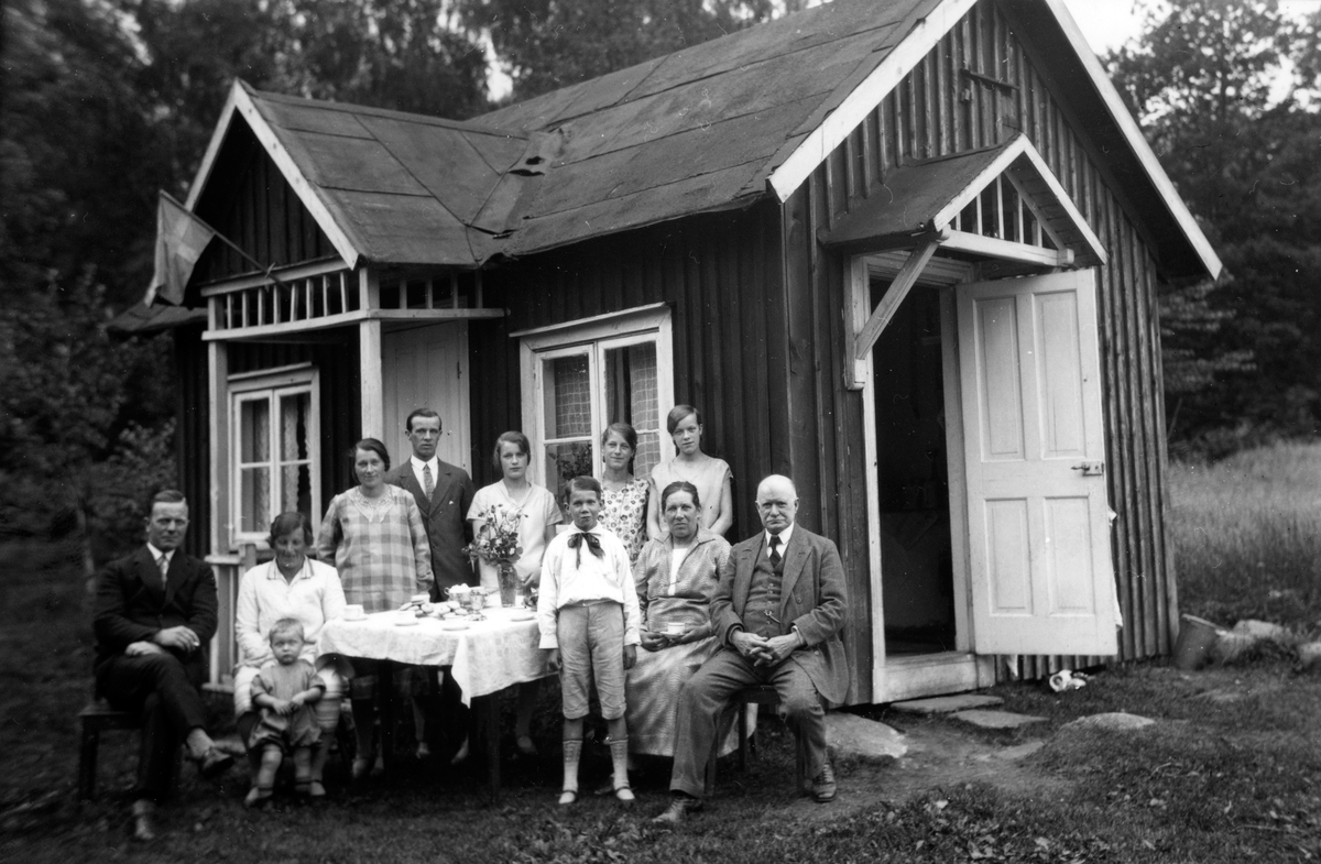 Födelsedagsfirande utanför stugan i Kortebo i Jönköping. Stugan ägdes av Klara Johansson och hyrdes av Signe Halldin och hennes make. På bilden sitter de till vänster med sonen Per-Olof. De övriga är Signes föräldrar och syskon.