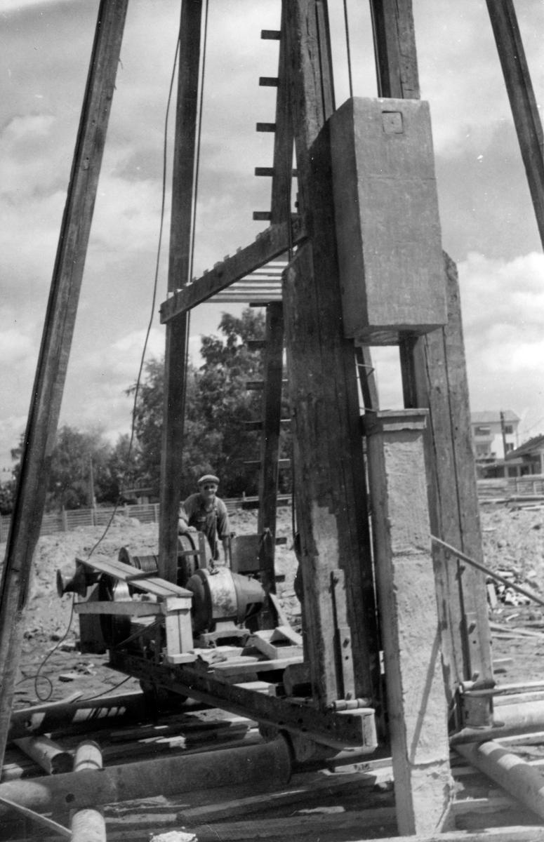 Tre män, utan hörselskydd, vid en maskinell grundpålning för husbygge i Jönköping.