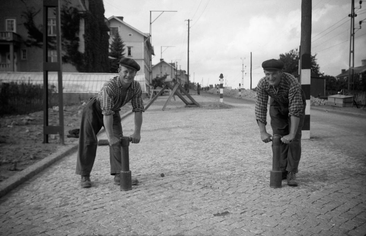 Gatuarbete på Kortebovägen i Jönköping. Från vänster: Bengt Johansson och Karl Fagerberg. Stöten de håller i (jungfrun kallad) vägde närmare 50 kilo. I bakgrunden syns Erikssons växthus, Jönköpings plantskola.