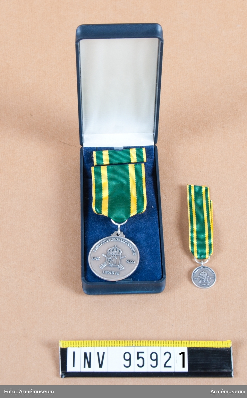 Lapplands jägarregementes ( I 22/Fo66) minnesmedalj i silver, 8:e storleken, 2000. Band: grönt med smala gula kanter och en gul rand på vardera sidan.  Medalj, miniatyrmedalj och släpspänne i blå ask klädd med blå sammet och vit siden.