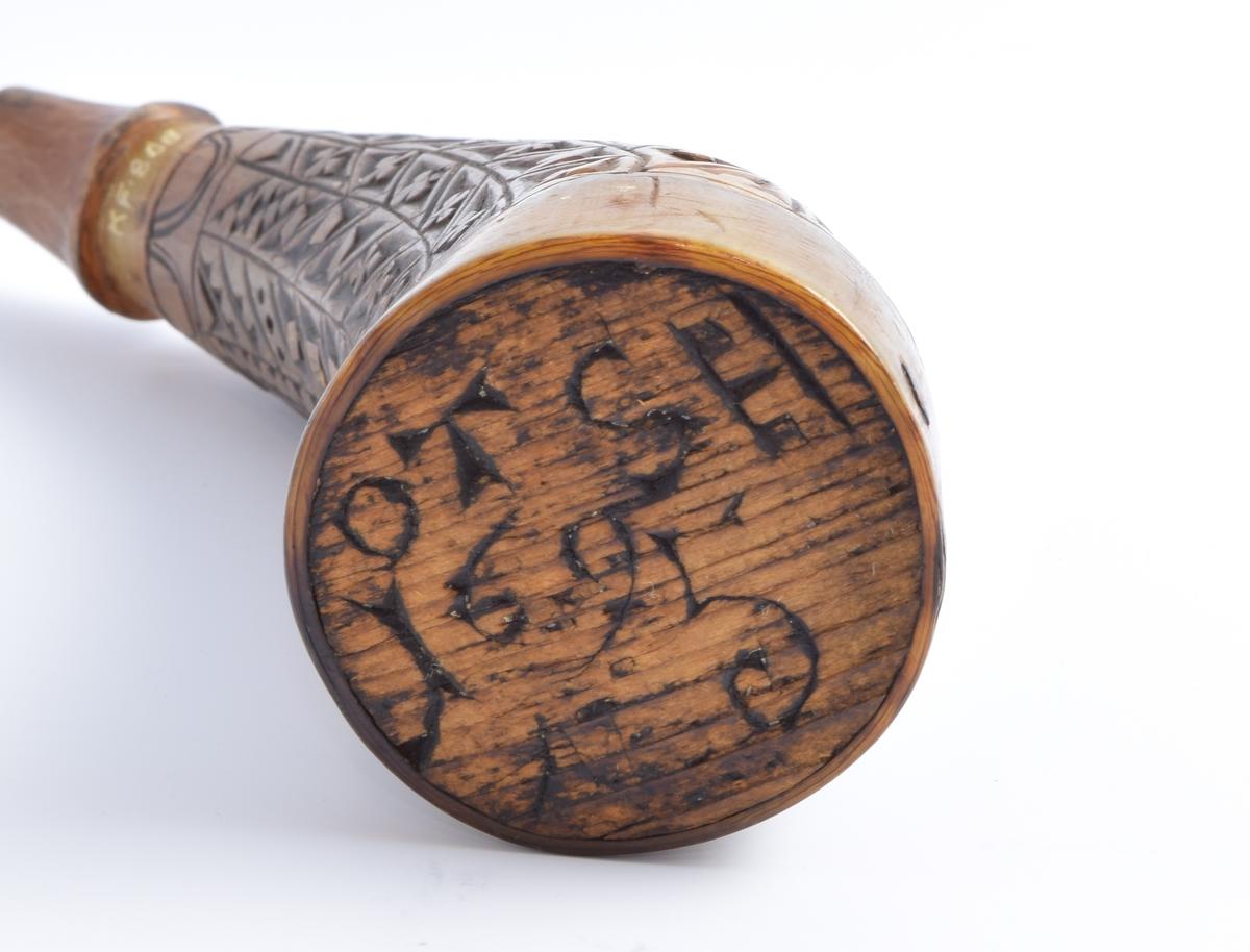 Lett krumt krutthorn med skårne dekorasjoner i form av langsgående striper delt inn i romber med en korsblomst i hver.