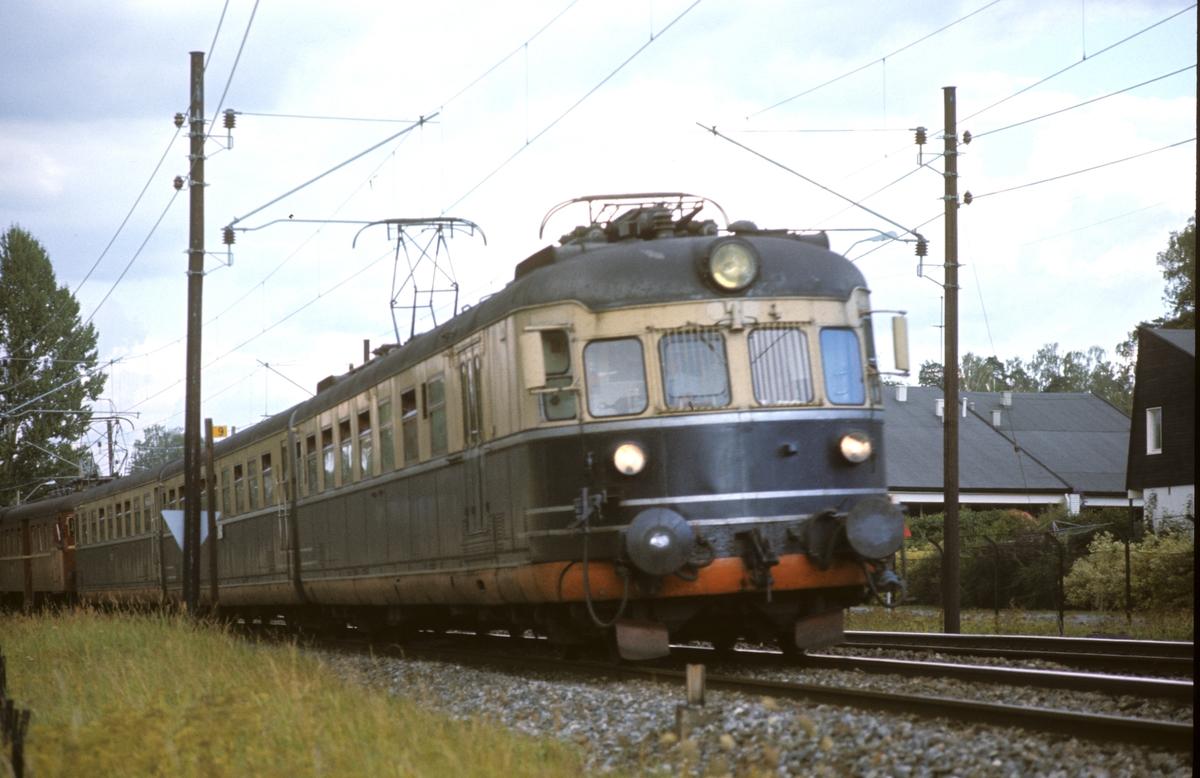 NSB elektrisk ekspresstog type 66, lyntog, motorvogn BM 66 01 nærmest, mellom Stabekk og Høvik stasjoner. Hurtigtog 811 til Vestfoldbanen. Bakerste togsett type 68A ble koblet av i Drammen og gikk til Vestfossen.
