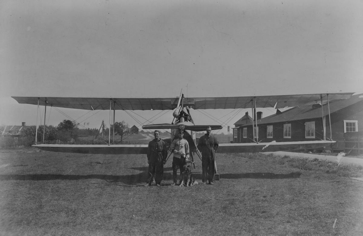 Grupporträtt. Tre militärer och en hund står framför flygplan Albatros BIIa på ett flygfält. Två av militärerna är klädda i flygardräkt.