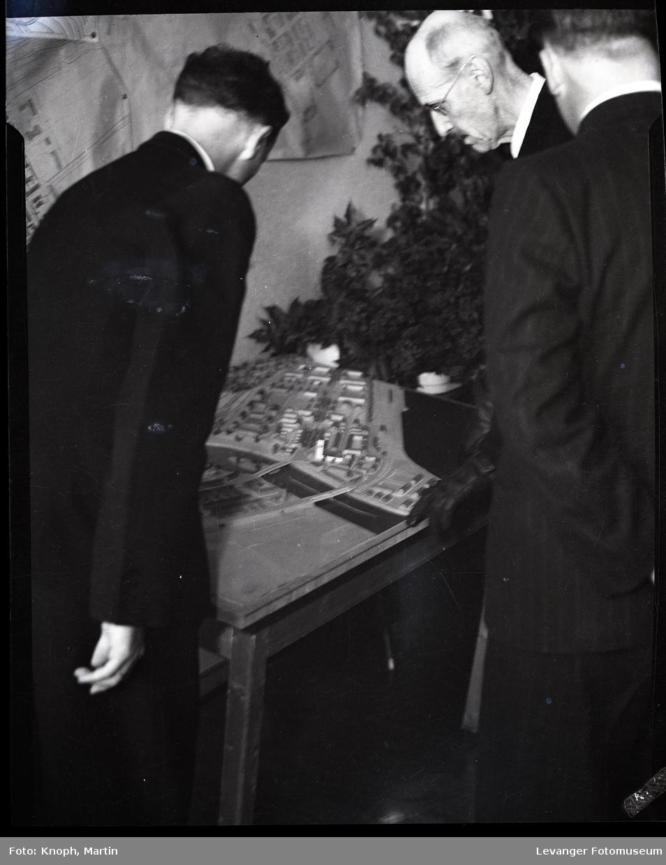 Kongelig besøk, kong Haakon besiktiger modell av Steinkjer i forbindelse med gjenreisningen.