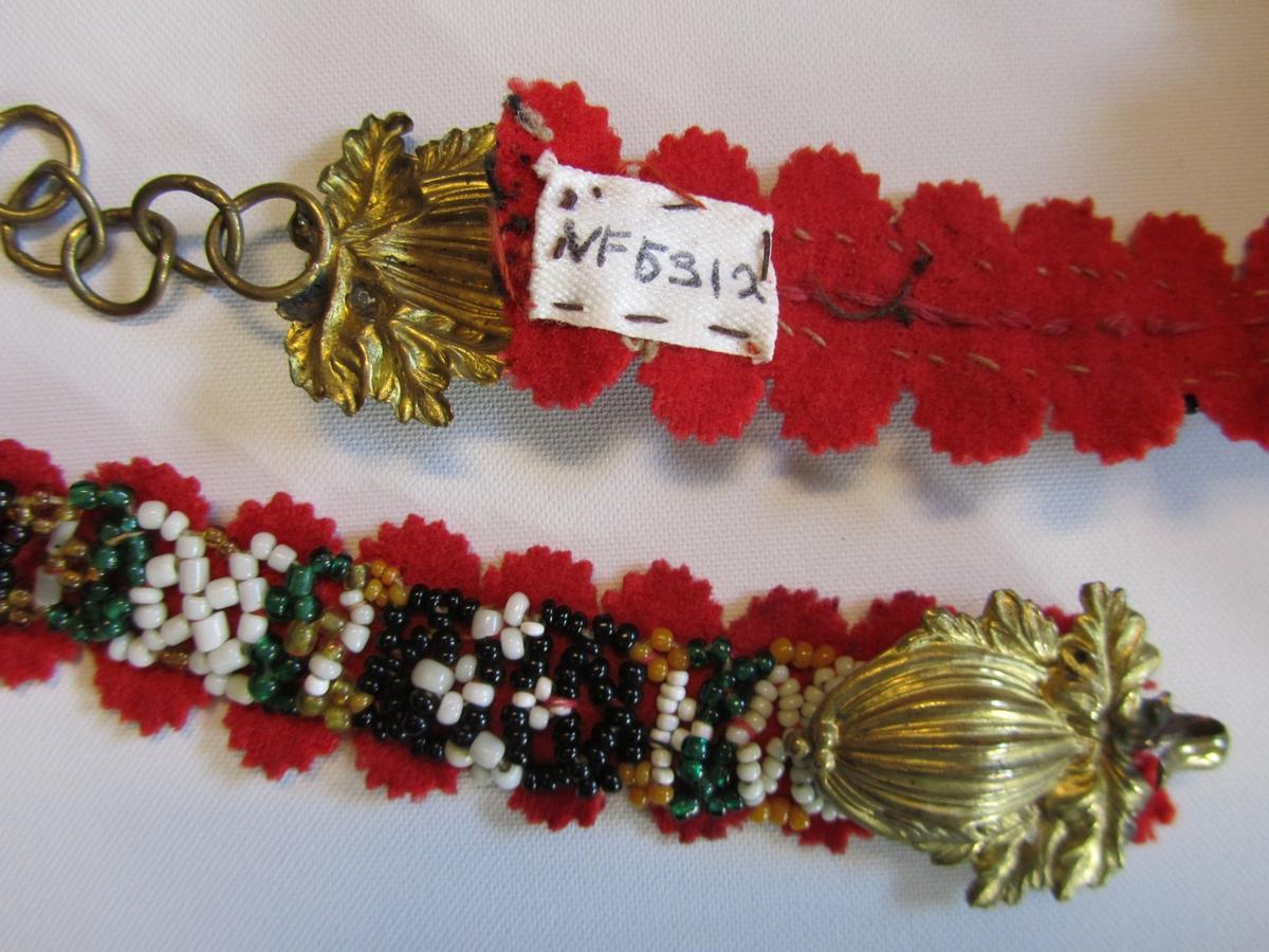 Perlebelte med bunn av rødt klede. Tredd band av småperler i forskjellige farger. Langsidene har utstansa små taggekantar ca 1 cm i diameter.  Er innbretta i kvar ende, og har messingspenne .