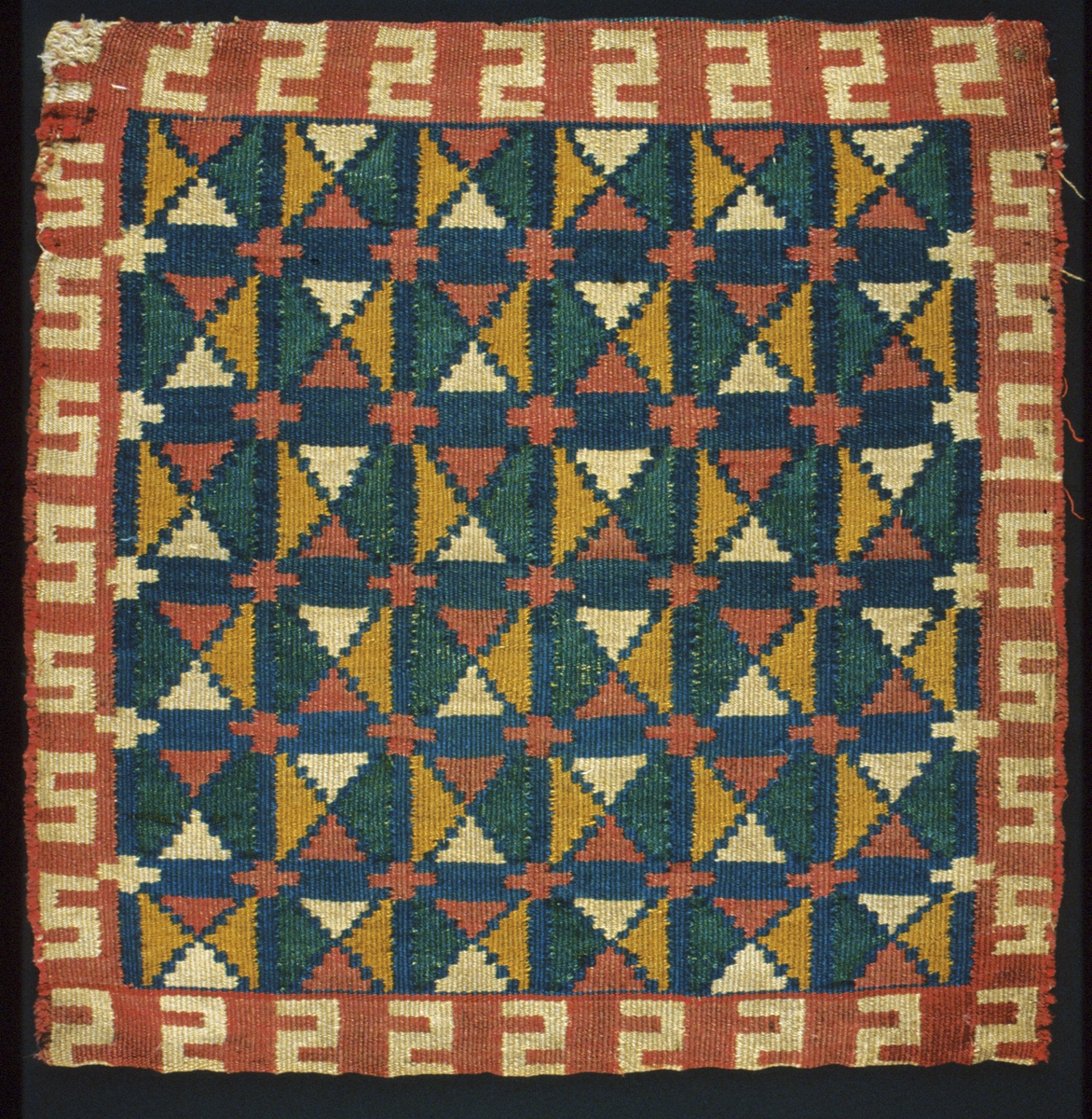 """Dyna/jynne vävd i rölakan. Ytmönster av kvadrater uppbyggda av fyra trianglar i grönt, blårött/rosa, gult och naturvitt på blå botten. Runt om löper en naturvit S-bård på blåröd/rosa botten.  Varp i 2-trådigt s-spunnet lingarn, 5 trådar/cm. Inslag i 1-trådigt s-spunnet ullgarn, dubbelspolat. Bakstycke i randigt ylletyg vävt i tuskaft, i grönt, lila, blått och brunt.Öppen i ena långsidan. Rester av dun inuti. Märkt med påsydd tyglapp med texten: """"Inköpt Landstinget  N° 3.  a""""."""