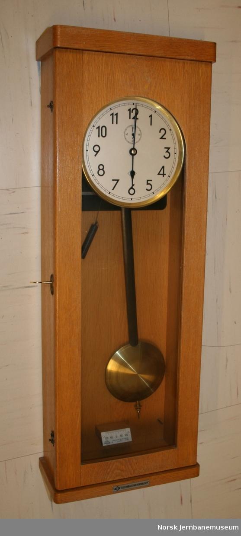 Veggur - pendelur i trekasse, sannsynligvis brukt på stasjonskontor.