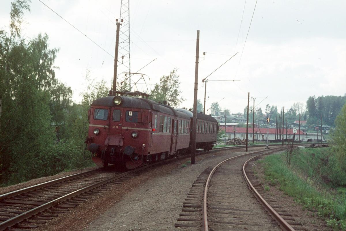 """Persontog fra Østfoldbanen Østre linje kjører inn på Ski stasjon. Motorvognsett type 65 med styrevogn """"ubåt"""" BFS 65 og motorvogn BM 65B 31. Spornummersignal viser at toget skal kjøre til spor 1."""