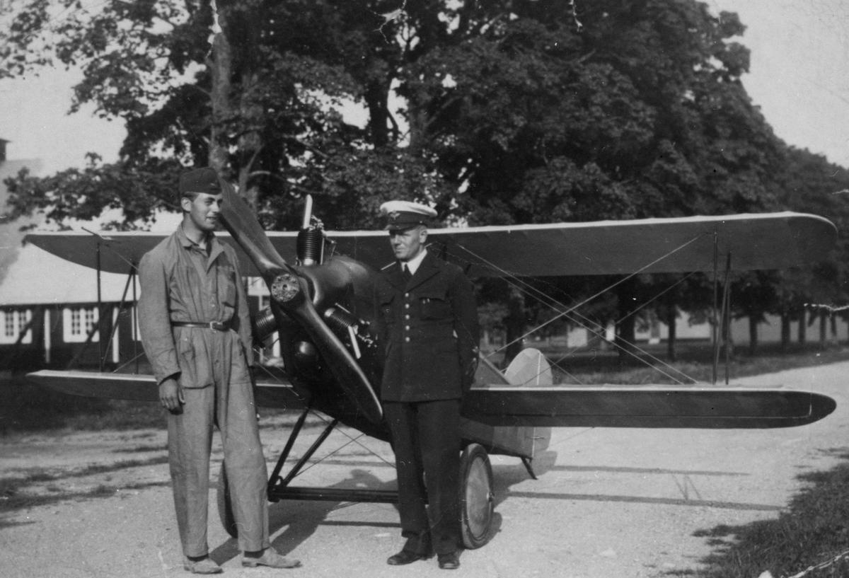 Porträtt. Två militärer framför det civila flygplanet Holmberg Racer på Malmen. Flygplanet var ett hemmabygge av tyghantverkare George Holmberg, till höger.