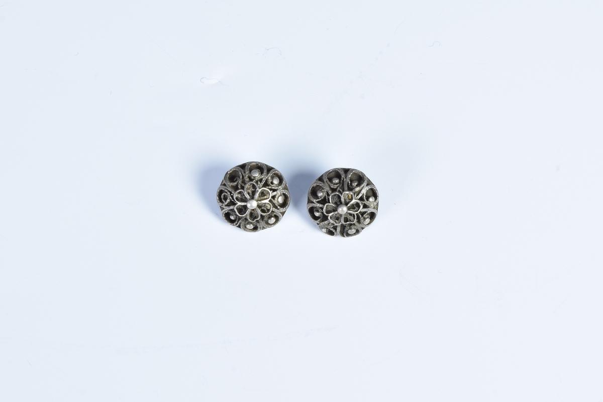 To knapper av sølv med filigransarbeid.