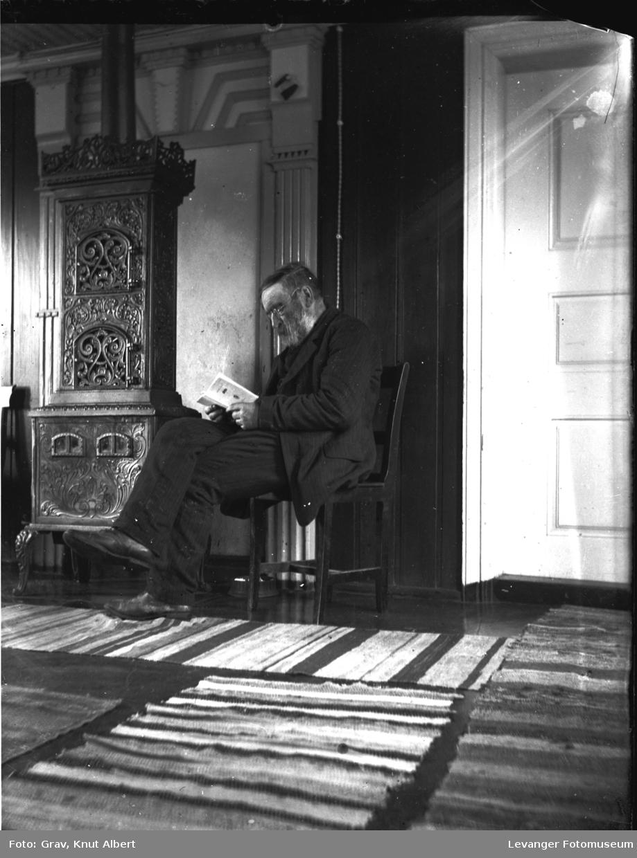 Interiør. portrett av mann som leser bok.