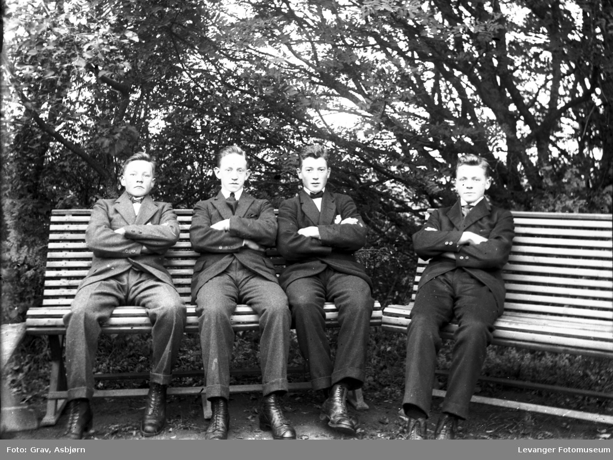 Gruppebilde, fire unge menn på benker i hage.
