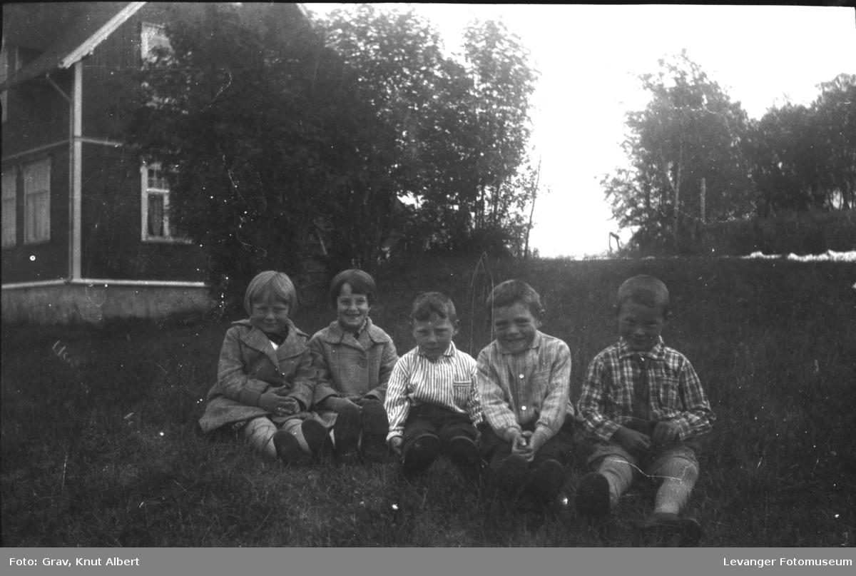 Gruppebilde, fem barn sitter på bakken.