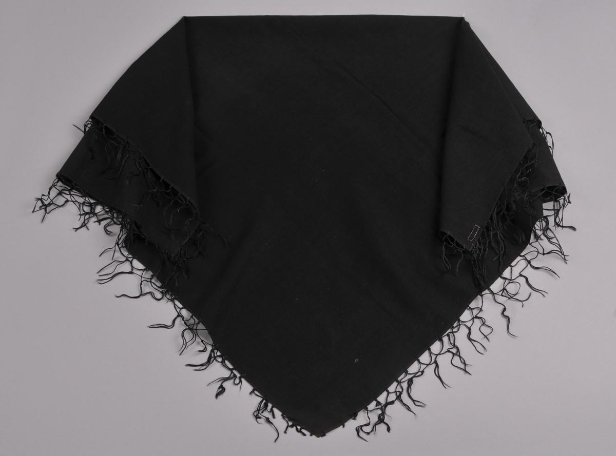 Tørkle av tynt svart ullstoff med silkefrynser. Dobbel fald i to sider sauma med maskin, jarekant i dei to andre sidene. Knytte frynser.