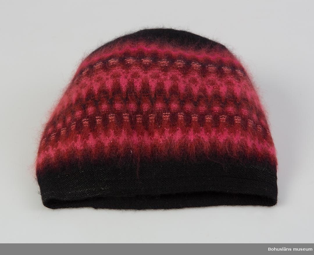 Mössa i mönster Nya Azalean i design av Kerstin Olson efter 1963. Angoragarn i  färgerna ceriserött, mörkrött, vinrött, svart, rosa och ljust rosa.  Modellen kallas sotarmössa.