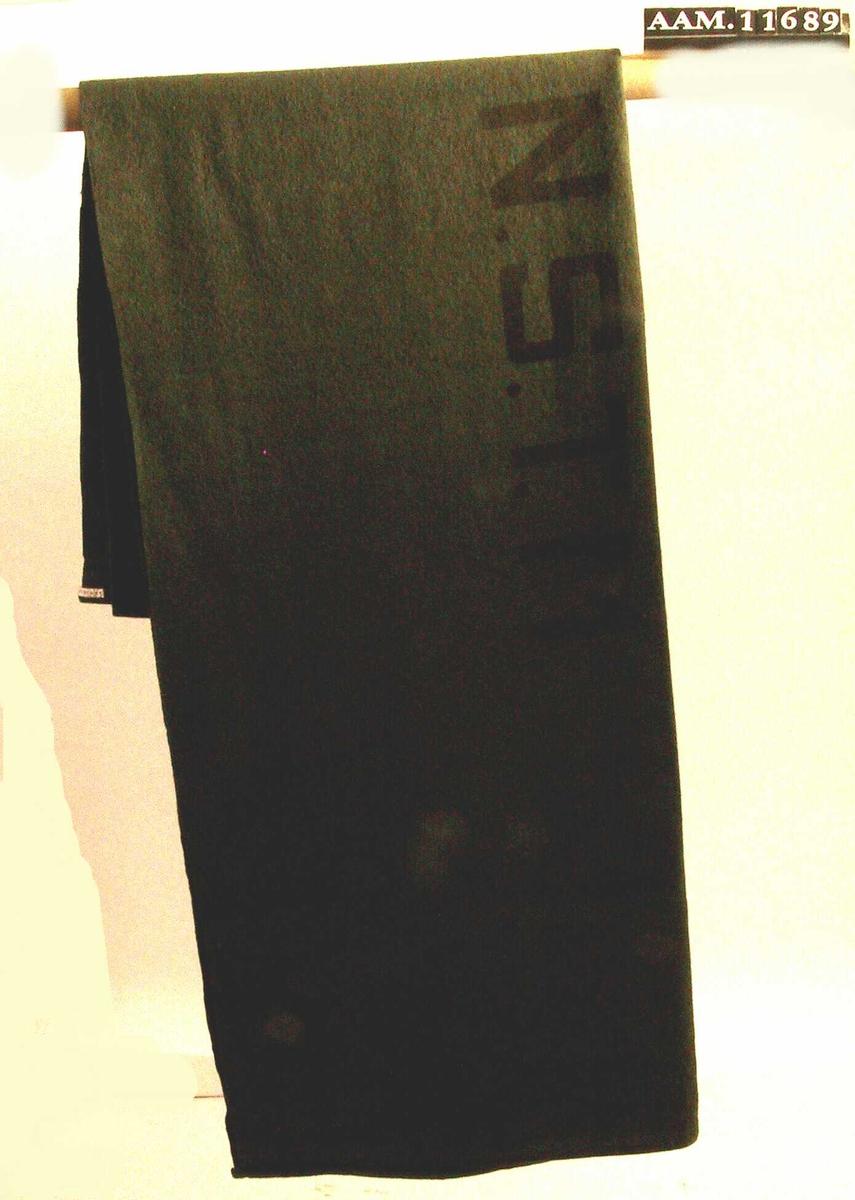 Militærgrønn ull, maskinsøm. Stort korthåret teppe, merket med store bokstaver  i sort:  det norske statsstyrte rederiet, som besto  av skip i den norske handelsflåte som ikke var i norsk  havn 9. april 1940.