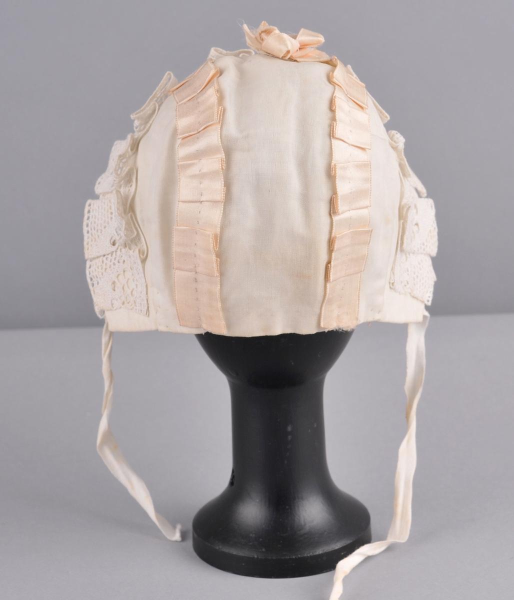 Kvit trestykks-luve; eit midtstykke frå panne til nakke med to avrunda firkanta sidestykke. Luva er av lin som er kledd med kvit voile. Over saumane er det eit foldelagt ljosrosa silkeband. Midt på hovudet er det ein rosett av same type silkeband. Langs framkanten på luva er det ein kvit foldelagt linknipling. Innerluva som er sauma fast nokre stader på sjølve luva, er av bomullsbatist og har eit anna snitt; eit rektangulært stoffstykke som har saum i nakken og rynker på issen. Det er linknipling i framkant på underluva. Knytebanda er kvite bomullsband.