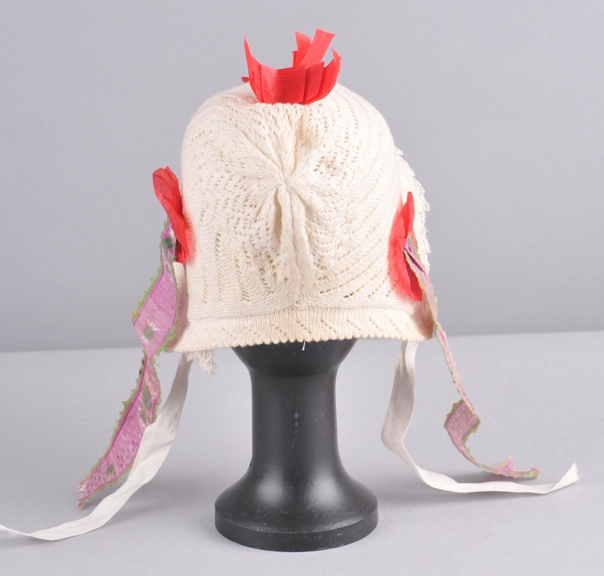 Maskinstrikka, fabrikkert, kvit luve av bomull. Luva har kyseform og fastsauma innerluve med synleg blondekant. Luva er mønsterstrikka og dekorert med raude silkeband, to sløyfer på toppen av luva og ein rosett på kvar side av luva. På rosettane er det  sauma fast silkeband i lilla, grønt og kvitt. Desse banda heng ned, eit  på kvar side, paralellt med knytebanda på luva. Innerluva er av bomullslerret. Luva er av to stykke og har saum midt på hovudet, i nakken og er rynka på issen. Framover har luva legg og ein dobbel kant med blonder der den eine blonda visar berre på vronga. Mot nakken har luva dobbel fald og legg. Knyteband av kvite bomullsband.