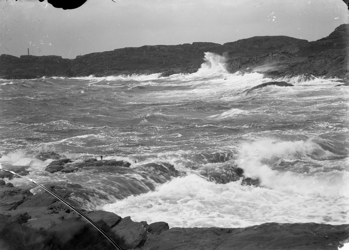 Sjø med bølger som slår inn mot land i Gardsvik (?). Fyrtårn til venstre (?) og steinkorset på Gard (?) (midt på bildet). Fjell i bakgrunnen.