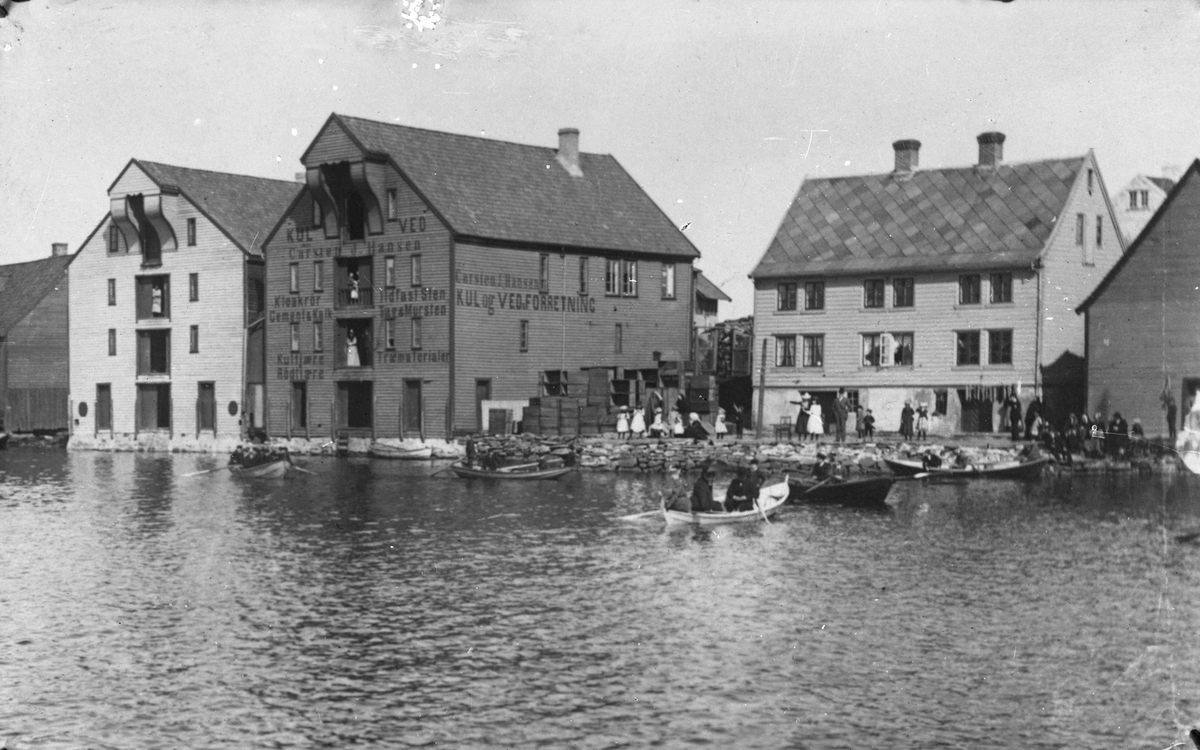 Sjur Lothes våningshus på Hasseløy. Flere færinger med flere persomer ombord. Trekasser stablet oppå hverandre på kaien. Det står også flere personer, inkludert noen barn, på kaien.