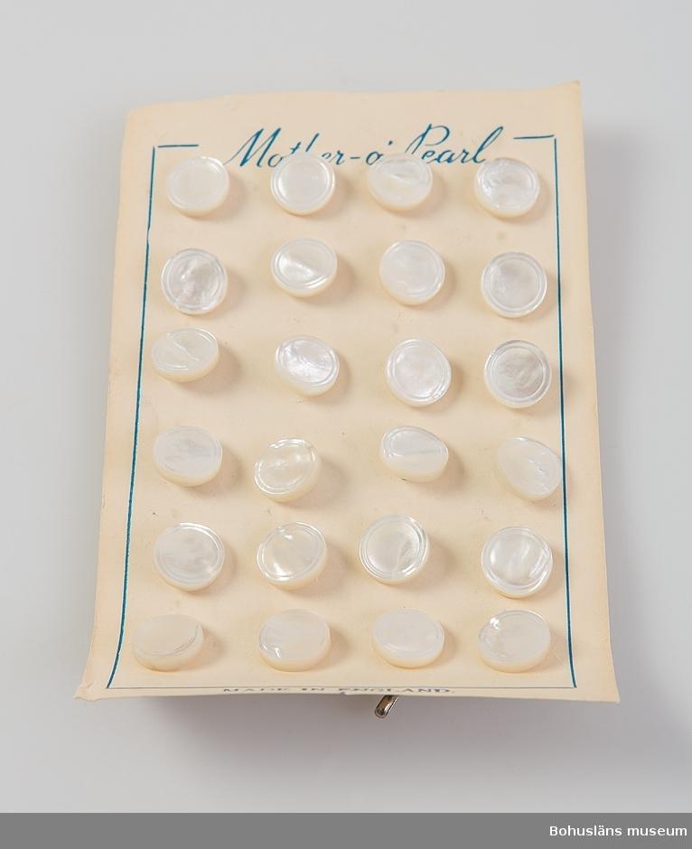En uppsättningar med 30 fastsatta skjortknappar av vit pärlemo fastsatta mot kartongblad. På framsidan tryckt text: Mother - o -pearl samt MADE IN ENGLAND. Knapparna har en yttre dekorrand i relief. På baksidan ögla med rostfri klammer.