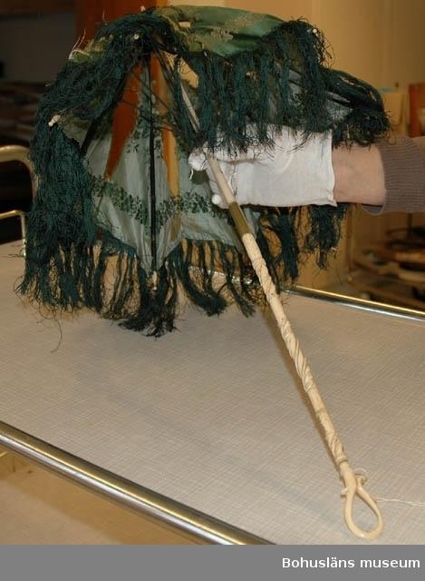 """Enligt gåvobok """"Parasoll från slutet av 1700-talet Uddevalla"""". Uppgiften är troligen inte korrekt. Från 1800-talets mitt är mer troligt. Bilderna visar i vilket skick parasollets siden var på 2000-talets mitt.  Ur handskrivna katalogen 1957-1958: Parasoll fr. slutet av 1700-t. Skaftets L. 66 cm; grönt siden m. fransar; skaftet av vitt ben, hopfällbar; tyget trasigt.  Lappkatalog: 81"""