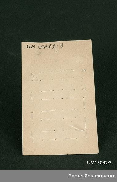 """Karta med 9 fastsydda kragknappar. Märken efter att det funnits ytterligare 3 knappar. Karta av trähaltigt papper med grått tryck, """"Nouveauté"""" plus ram i vitt. Knappar av vit konstharts och mässing."""