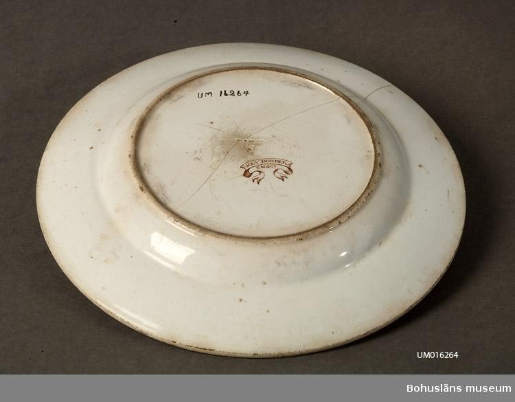 Tallrik, vit och brun. Brättet i linjer i brunt och vitt. Tallriken sprucken. Märkt Key border, SM 260.
