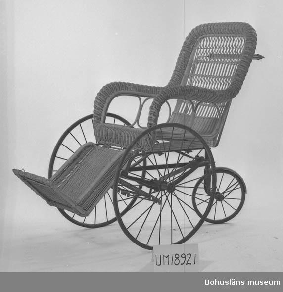 Rullstol med två stora och ett litet hjul i järn. Reglerbart fotstöd. Flätad sits, rygg och armstöd. Hjulen har metallekrar. Handtag bak ryggpartiet svarvat i trä. De flätade delarna är beigelackerade och målningen avflagnad. Hjulen har massiva gummiringar. Det bakre mindre hjulet är rörligt också i sidled.  Sittytan har ram av trä.