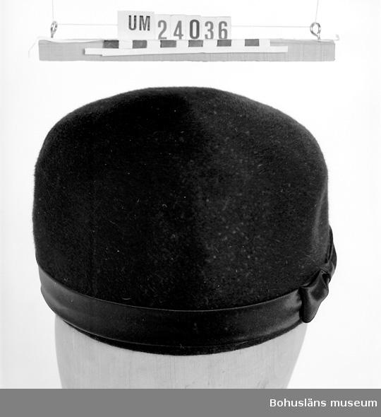471 Tillverkningstid 1961-1967 594 Landskap BOHUSLÄN 394 Landskap BOHUSLÄN 601 Hög rak hattmodell utan brätten. Svart filt och med svart sidenband 602 längs nederkant. Rosett framtill. Använd vid begravningar. Sorgslöja 603 finns se UM 24037. 604 Pillerburksmodell.