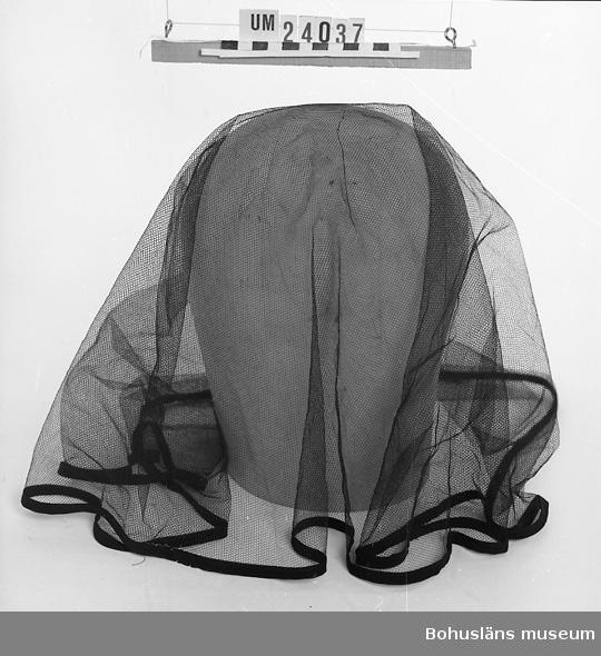 471 Tillverkningstid 1961-1967 410 Mått/Vikt !L:63 B:73 CM 594 Landskap BOHUSLÄN 601 Sorgslöja i svart flor med svart bandkantning. Sammanhör med hatt 602 UM 24036.