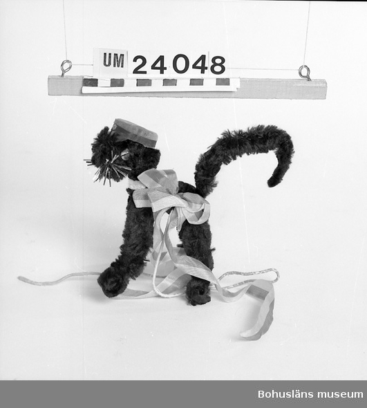 471 Tillverkningstid 1967 410 Mått/Vikt !H:49 B:10 L: 10 CM 594 Landskap BOHUSLÄN 601 Katt (H: 17 cm) i svart plysch med plastögon, realmössa i sammet och 602 med blågul rosett med hängande band, fastsatt på sidan. Manhår av 603 någon typ av folie. Fastsatt på stång av lindad ståltråd. Satt in- 604 stucken i blombukett som givaren fick vid realexamen 1967. 605 Denna typ av prydnad vanlig i detta sammanhang vid realexamen. Upp- 606 hörde i stort sett i samband med att realexamen försvann i samband 607 med skolreformen under sent 1960-tal. Givaren/brukaren född 1951 på 608 Orust, Torp sn, sedan bosatt i Uddevalla.