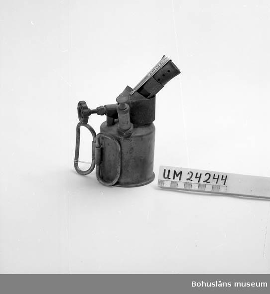 Metallbehållare. Utfällbara handtag. En kran. På munstycket för lågan hänger en rensnål.