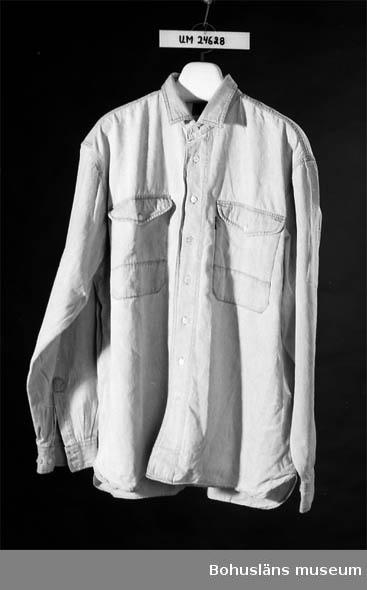 """Mått: Ärmlängd 50 cm Ljusblå jeansliknande tyg. Två bröstfickor. Knäppes med 8 st vita plastknappar framtill. Svart tryck på ryggen: """"HOT HOT TOTTA & THE HOT""""N""""TOTS"""", """"dobber MATS SPORT"""". Tygetikett vid vänstra bröstfickan, text: """"dobber"""". Tygetikett i nacken, text: """"dobber QUALITY CLOTHING"""". På insidan i ena sidosömmen finns en lapp med tvättinstruktioner."""