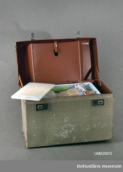 Lådan är en sk. konduktörsväska. Svart, vit och beige rutig. Bruna detaljer. Brun inuti. Tre fack. Ett fack i locket. Har använts vid camping från 1961 - 1991. Innehåll: Ljusblå besticklåda, visp med grönt handtag, plastlock till tetrapak, potatisskalare, 3 st kapsyler av plast, kniv, konservöpp- nare, träslev, kniv, slickepott av trä, ostskärare, påse med reserv- tråd till ostskärare, 2 st teskedar, 4 st matskedar, 4 st gafflar, 4 st knivar, 2 st smörknivar, 1 st påläggsgaffel, flasköppnare, prov- sticka, en burk med salt, en burk med vitpeppar, en burk med allkryd- da, gult plastfodral med brynsten, vit dossked av plast, plastpåse med 13 st böjda metallspikar*, plastpåse med 8 st konservöppnare, skärbräda av ljus plast, 4 st vita plasttallrikar, 4 st blå plasttallrikar, ljusgult tefat, 2 st röda assietter, 2 st gula assietter, 4 st vita äggkoppar, vit förvaringsburk till kaffe svart lock och röd dossked, vit förvaringsburk till socker svart lock gul dossked, förvaringsburk till lingon svart, förvaringsburk till havregryn vit med svart lock och gul dossked, förvaringsburk för müsslie vit med svart lock och grön dossked, förvaringsburk för vetemjöl vit med svart lock och vit dossked, förvaringsburk till salt vit med svart lock och vit dossked, rund förvaringsburk med platt lock, 2 st röda muggar med vit kant, 2 st gula muggar med vit kant, 3 st genomskinliga dricksglas av plast med röda äpplen, genomskinligt dricksglas av plast. Tesil av metall, behållare för tesilen av metall, decilitermått av metall, 4 st papperspåsar, 7 st lösa plastpåsar, en rulle med plastpåsar och en ask med tandpetare.  *)Använda till att spika upp i hytta om man hyrde och det ej fanns handdukshängare.  Intervju med Stig Börjesson förvaras i Enskilda arkiv. Föremål för camping, sportfiske och skidåkning från samma givare, se: UM23741-UM23750, UM24196, UM24232-UM24248, UM24251, UM24634,UM24635, UM24790, UM25065 – UM25074.