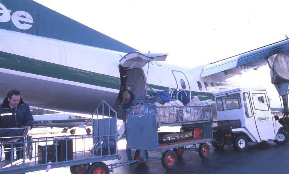 Lufthavn/Flyplass. Sogndal. Ett fly, LN-WFL, DHC-7-102 / Dash7 fra Widerøe losses for frakt og bagasje..