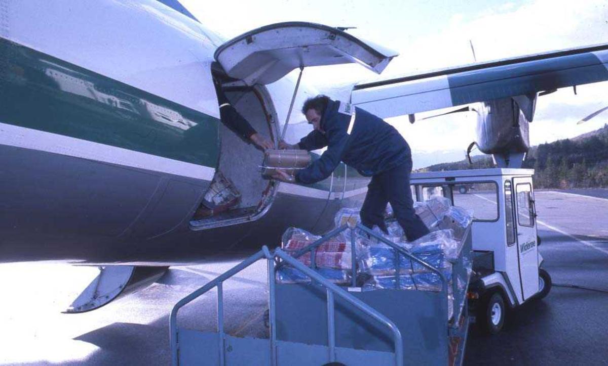 Lufthavn/flyplass. Sogndal. Ett fly, LN-WFL, DHC-7-102 / Dash7 fra Widerøe, losses for post, frakt og bagasje.