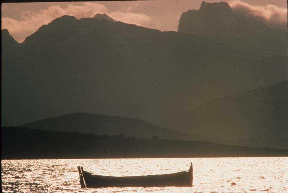 Landskap. Nordlandsbåt fortøyd på sjøen. Lyngsalpene i Troms  i bakgrunn.