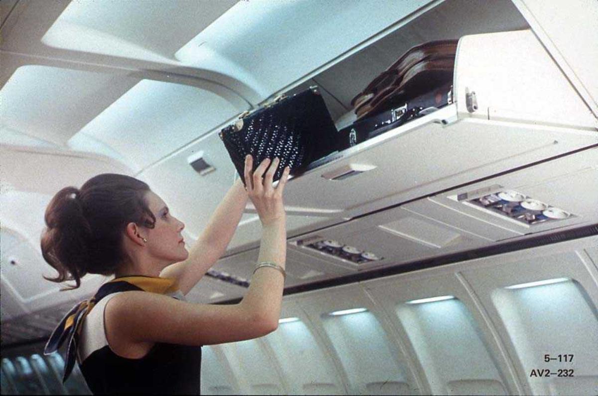 En person som legger en veske oppi hattehyllen på en Boeing 737-200.