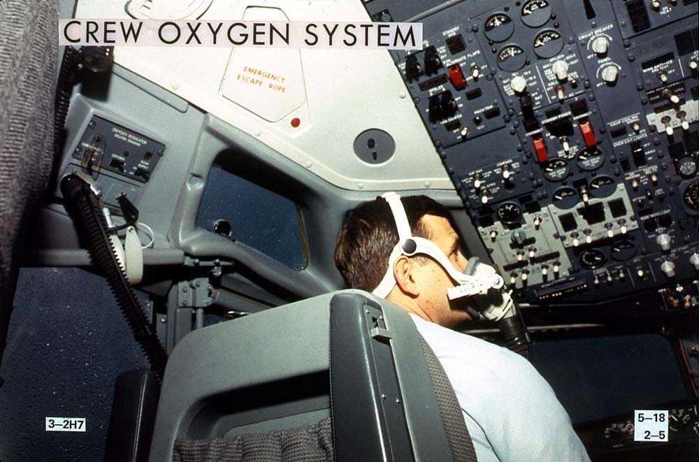 En person som sitter i cockpiten på en Boeing 737-200 med en oksygenmaske på seg.