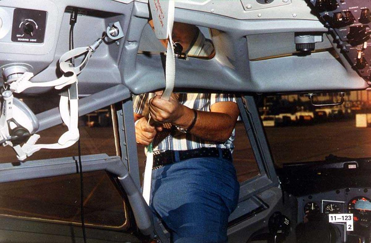 En person som henger i en nødevakueringsstropp i ett vindu i cockpiten på ett fly, Boeing 737-200.
