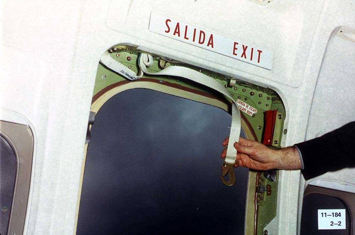Øvre del av en åpen nøddør på ett fly, Boeing 737-200. Et stropp med en krok øverst i døren.