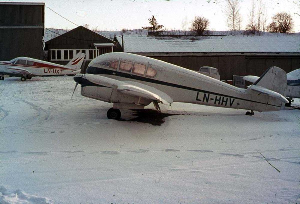 Ett fly på bakken, CZL Super Aero 45 LN-HHV. Bygninger og to fly i bakgrunnen. Snø på bakken.