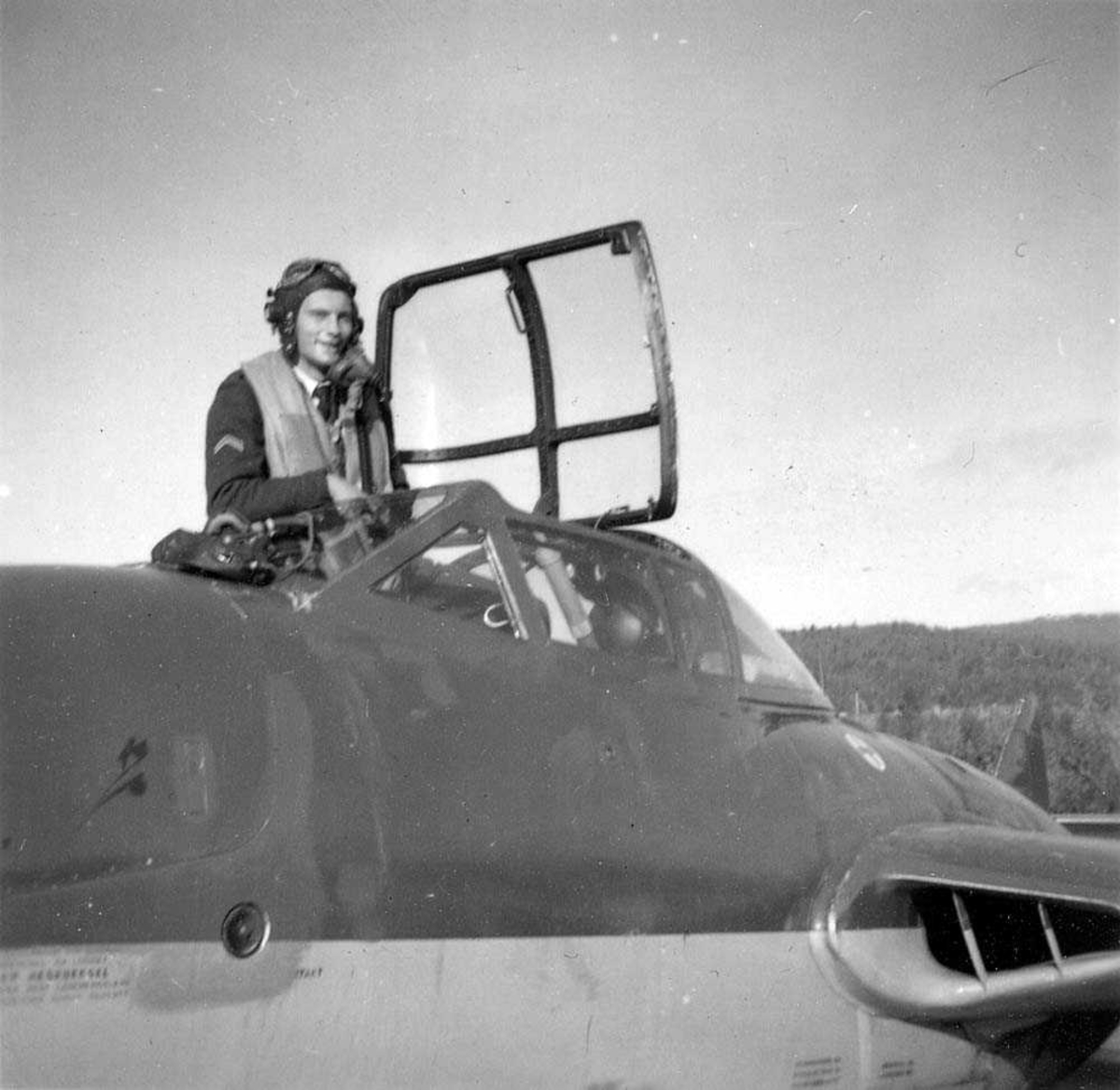En person som står i cockpiten på ett fly på bakken.