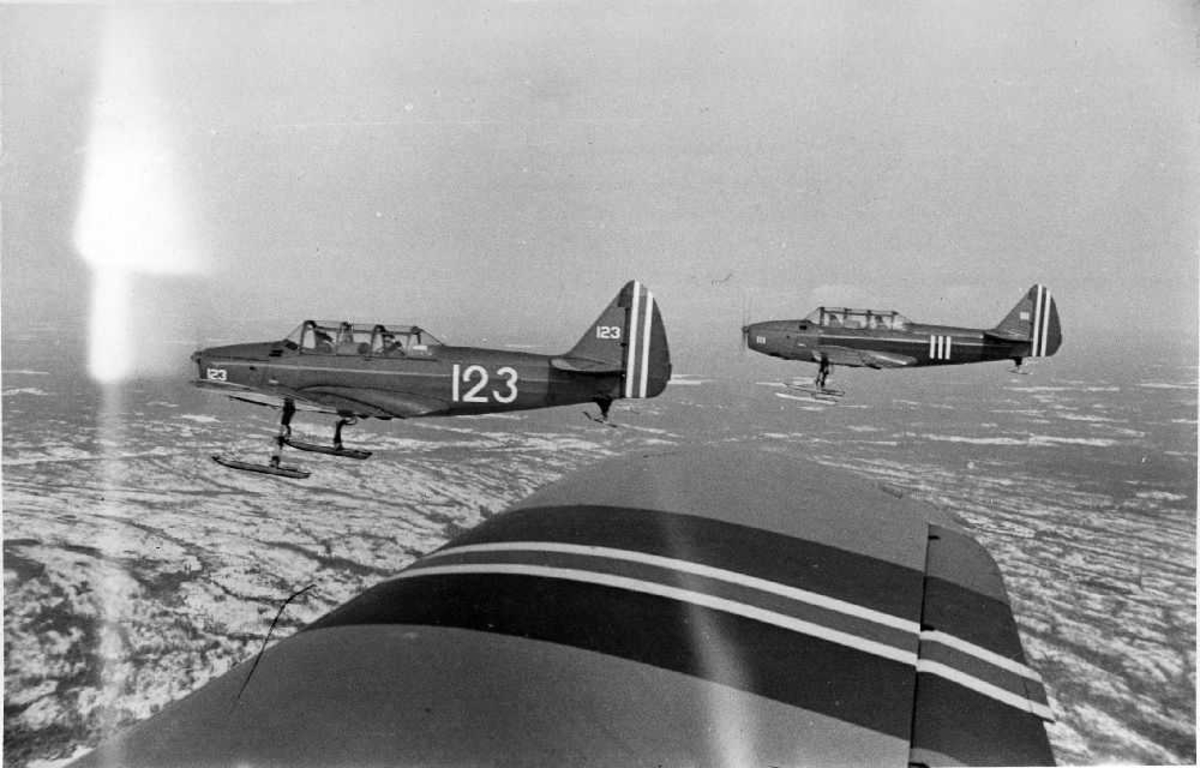 Luftfoto. Tre fly av typen Fairchild Cornell II, fra det Norske Luftforsvaret, foretar formasjonsflyging. Alle er utstyrt med skiunderstell. Fotografen sitter i det ene flyet. Under oss ligger bakken delvis dekket av snø.