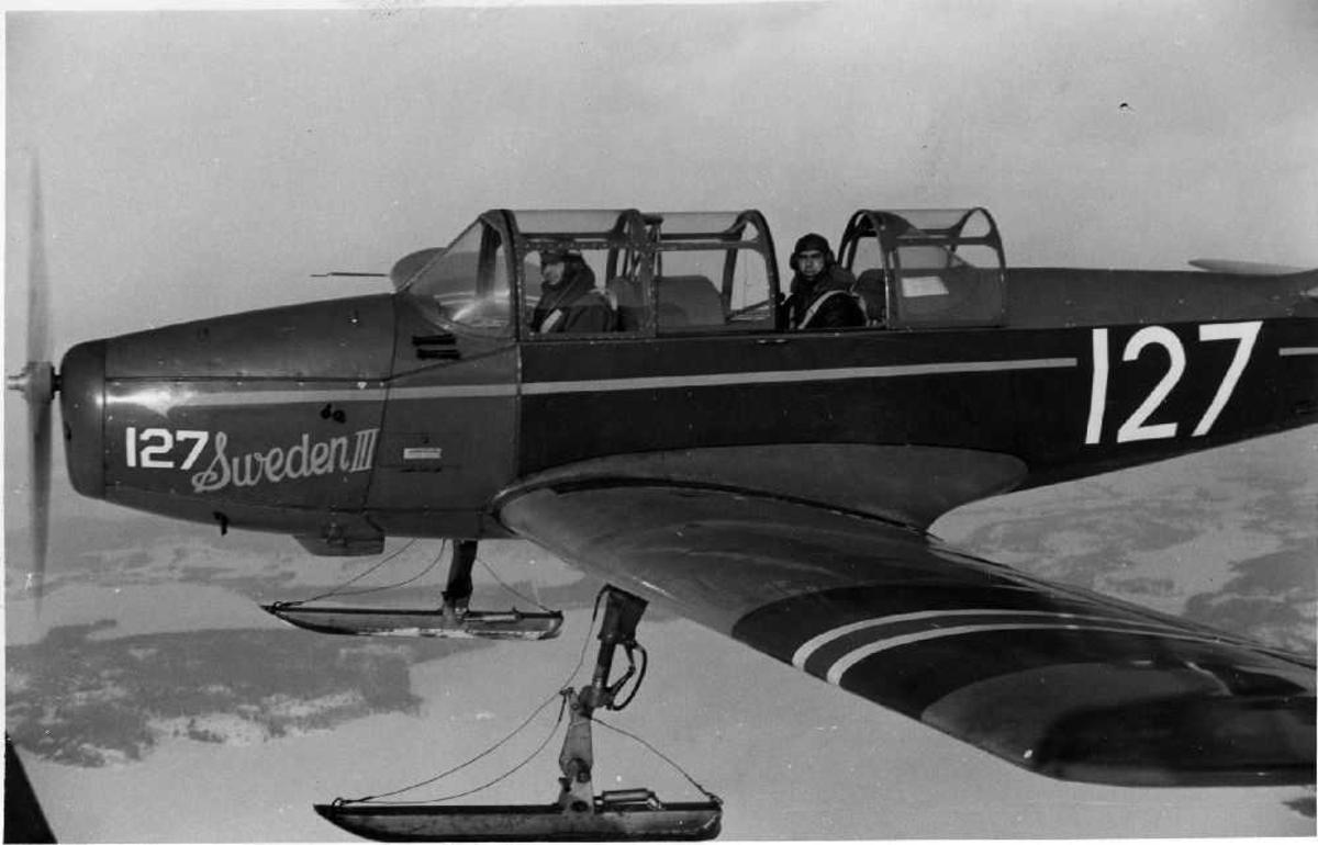 Luftfoto. Et fly av typen Fairshild Cornell II (127) fra Det Norske Luftforsvaret, ute på flytur. Flyet er utstyrt med skiunderstell. Ombord sitter to personer. Under oss ser vi islagte vann og snedekket natur.