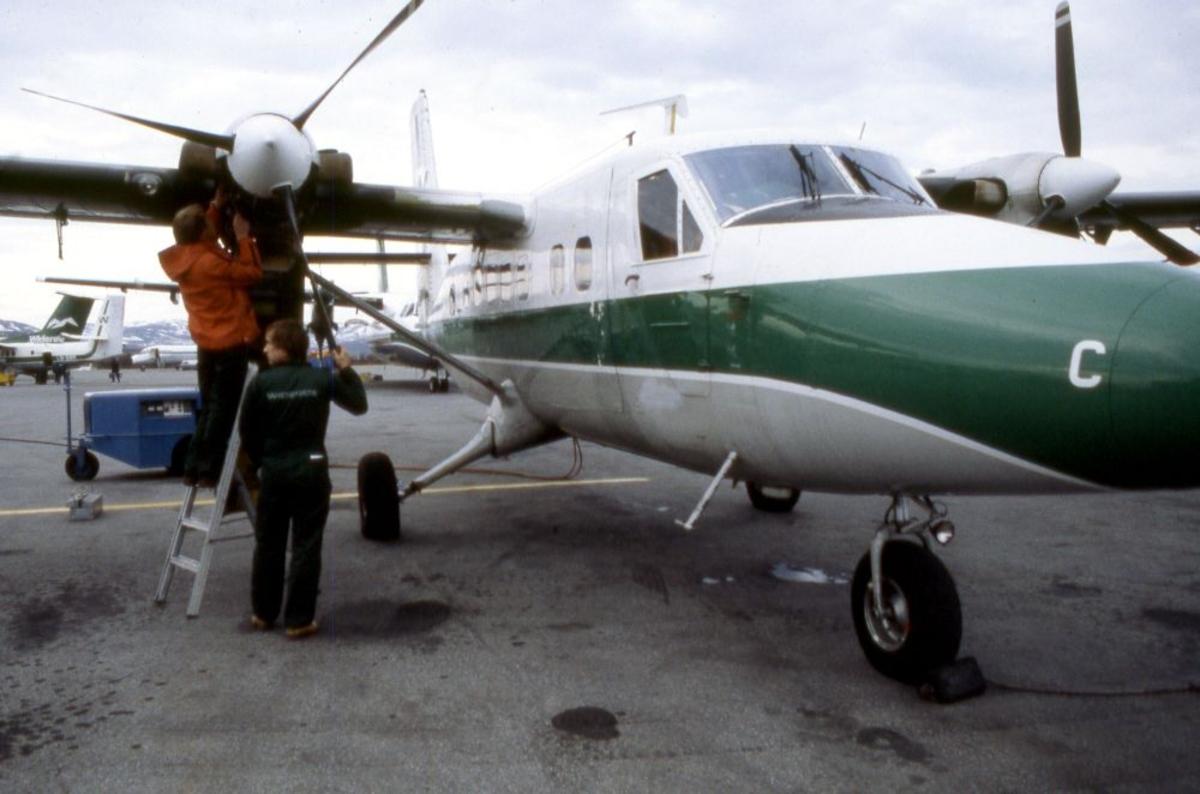 Lufthavn (flyplass) Flere fly parkert, bl.a. LN-WFC, DHC-6-300 Twin Otter fra Widerøe. To flyteknikere arbeider med høyre motor.