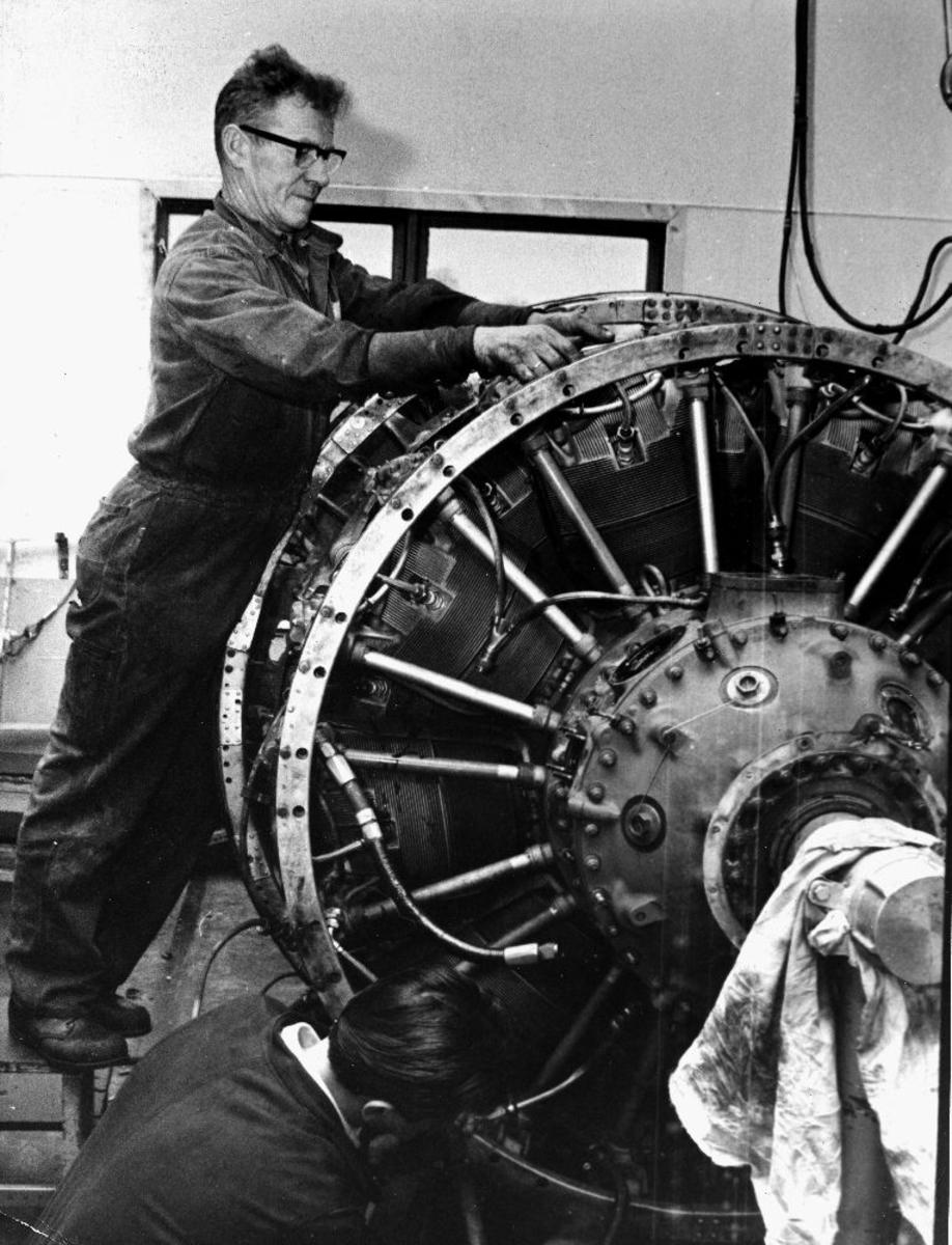 Lufthavn/flyplass. Sola/Stavanger. Motorverksted. To personer gjør vedlikeholder en flymotor til et fly fra Braathens SAFE.