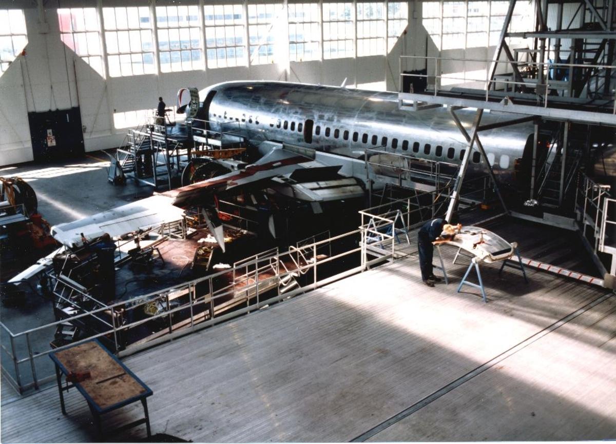 Lufthavn/flyplass. Fornebu. Fra Braathens SAFE's tekniske divisjon. Et fly inne til ettersyn/vedlikehold (heloverhaling). Flere personer i virksomhet.