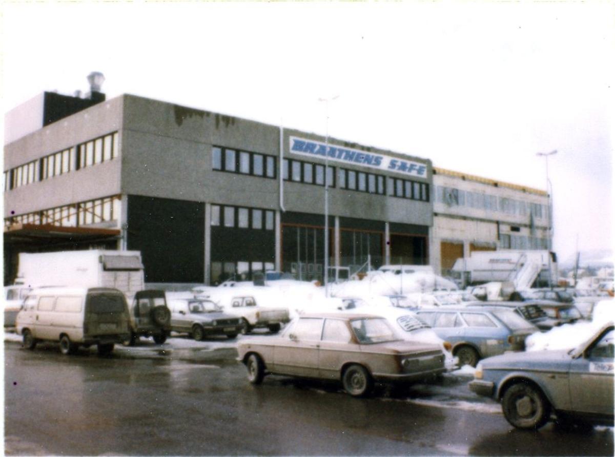 Landskap. Braathens SAFE`s Driftsbygg på Fornebu. På parkeringsplassen foran bygget er mange biler parkert.